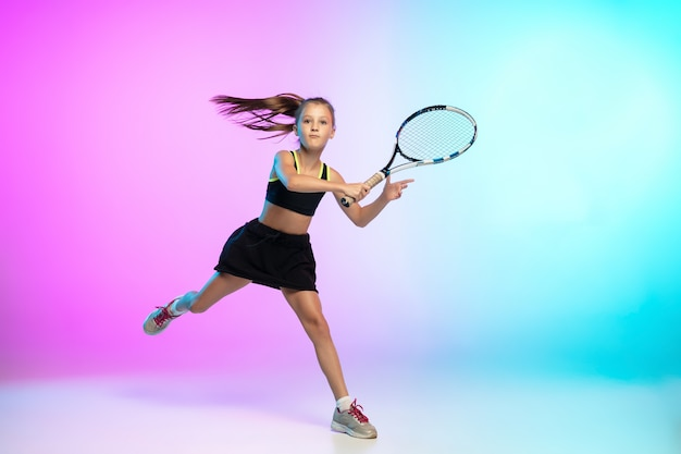 Training. little tennis girl in black sportwear isolated on gradient