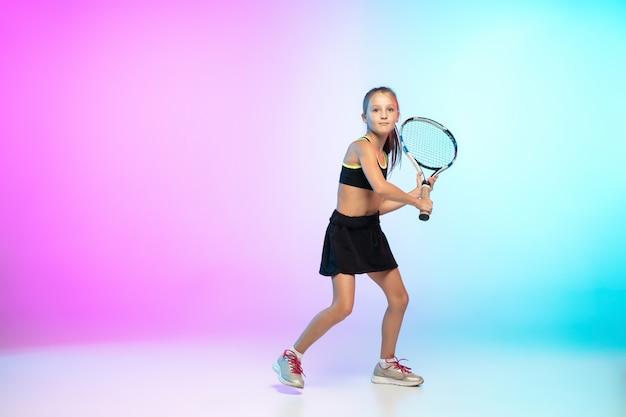 トレーニング。ネオンの光のグラデーションの背景に分離された黒いスポーツウェアの小さなテニスの女の子。白人モデル、運動と行動のスポーツキッズトレーニング。スポーツ、運動、子供の頃のコンセプト。