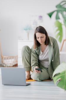 Тренировка медитации и йоги дома женщина делает физические упражнения с ноутбуком