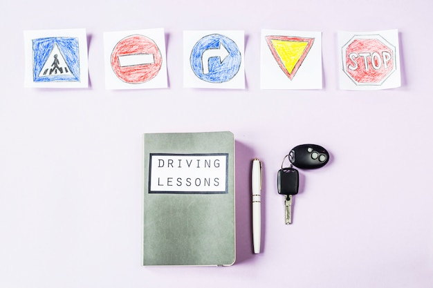 Training notebook for driving lessons and driving traffic rules next to the road sign drawings to get a driving license