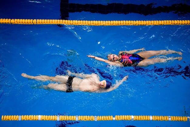 プロの水泳選手のトレーニング。アスリートはプールで仰向けに泳ぎます。