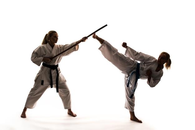 스포츠 장비와 가라데 스탠드를 사용하여 흰 기모노를 입은 두 소녀의 훈련. 흰색 배경에 고립