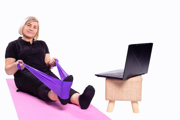 노트북을 사용하여 건강한 삶의 흐름을 위한 여성 노인 블로거 운동을 위해 홈 스포츠 취미에서 탄성 고무 밴드 체육관과 함께 요가 매트에서 온라인 개념 시니어 스포츠우먼 운동 훈련