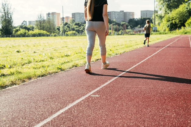 Training in an outdoor stadium. young woman walking on a red treadmill outside, back view. active lifestyle, weight loss