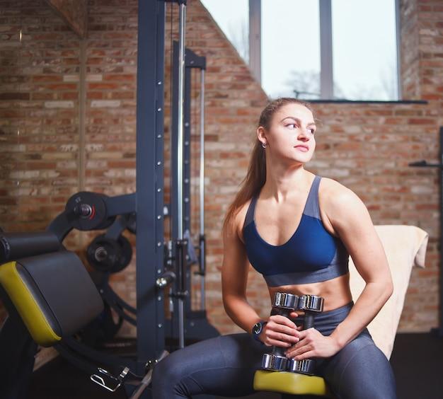 훈련 일시 정지. 운동복에 스포티 한 젊은 여성이 그녀의 손에 아령을 들고 벤치에서 쉬고 체육관에서 멀리보고