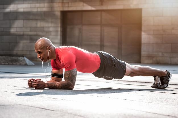 訓練計画。トレーニングをしながら腕立て伏せをしている強力な勤勉なスポーツマン