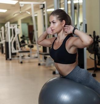 トレーニングプロセス。ジムでフィットボールにバックエクステンションを行うスポーツウエアで若いスポーツ女性