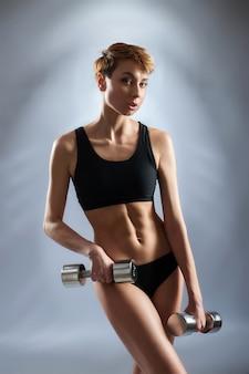 Режим тренировок. студийный портрет молодой коротко стриженной фитнес-женщины, позирующей с гантелями в руках, в спортивном бюстгальтере и шортах