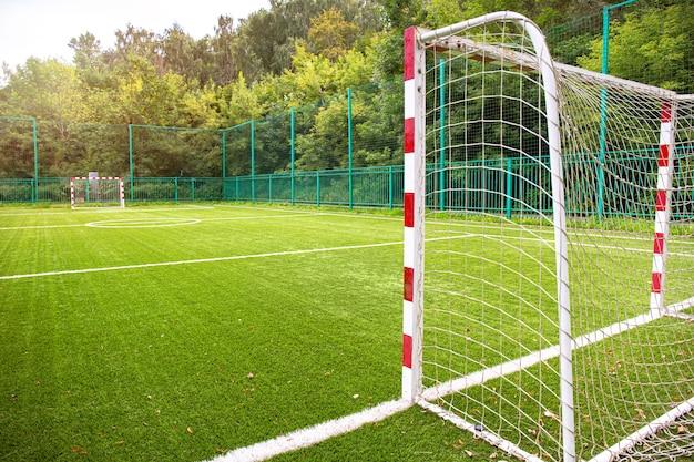 Тренировочное футбольное поле с зеленым покрытием. футбольное поле с воротами и разметкой или боковыми линиями.