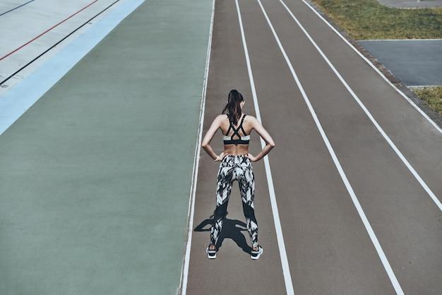 Обучение, чтобы стать лучшим. вид сверху сзади молодой женщины в спортивной одежде, держащей руки на бедрах