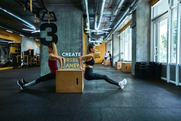 上腕三頭筋のトレーニング。ジムで木製のクロスフィットジャンプボックスで腕立て伏せをし、一緒に運動しているスポーツウェアの2人の若い運動女性の全長。陽気な人々、健康的なライフスタイルとトレーニングの概念