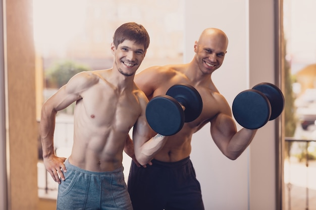 Training two men with dumbbells the arm muscles