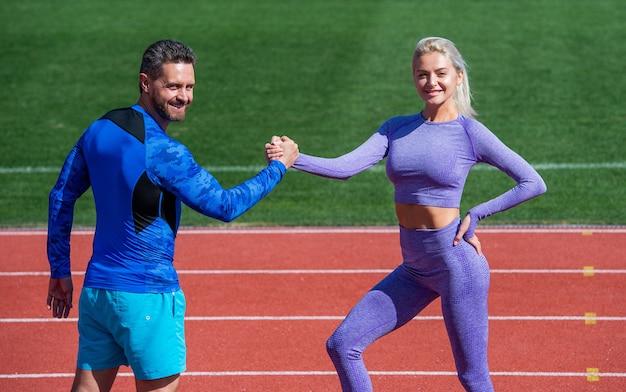 코치와 훈련. 피트니스 파트너. 운동 남자와 여자는 팔씨름에서 경쟁합니다. 경기장 실행 트랙 경기장에서 남성과 여성 코치. 건강한 생활. 행복한 스포츠 커플은 팀 승리를 축하합니다.