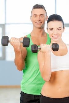 ダンベルを使ったトレーニング。ジムでダンベルを持ち上げて笑っているカップル