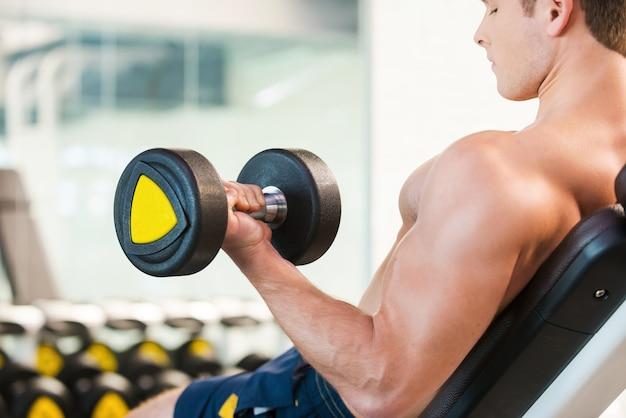 ダンベルを使ったトレーニング。ジムでダンベルを使ってトレーニングしている自信を持って若い筋肉の男の背面図