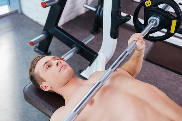 ウエイトを使ったトレーニング。ベンチプレスで働いている若い筋肉の男の上面図