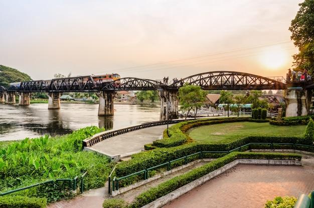 Поезда для путешествий, курсирующие по старому мосту через реку квай яй на закате, являются историческими достопримечательностями во время второй мировой войны знаменитой провинции канчанабури в таиланде.