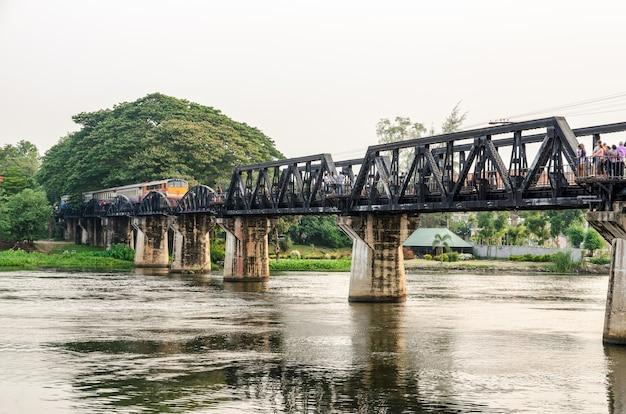 Поезда для путешествий, курсирующие по старому мосту через реку квай яй, являются исторической достопримечательностью во время второй мировой войны, известной провинции канчанабури в таиланде.