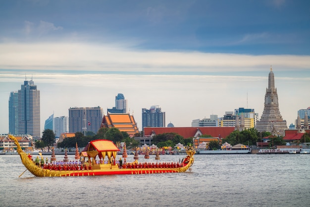 Traitional royal thai boat in river in bangkok city with wat arun temple