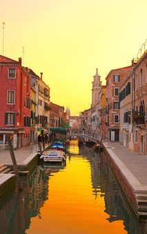 Traitional venice houses over water of small canal in old town at sunset, italy