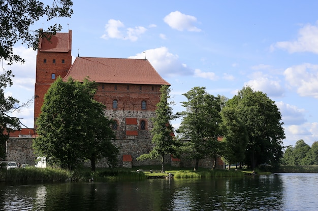 Trakai island castle, major tourist medieval attraction, reflecting in clear water of galve lake. white clouds
