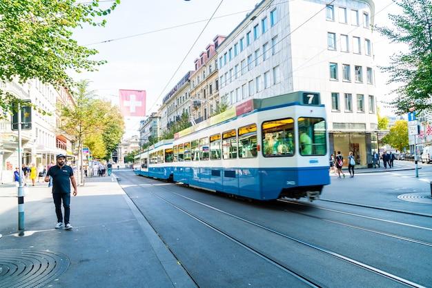 A tram drives down the center of bahnhofstrasse while people walk on the sidewalks in zurich, switzerland.