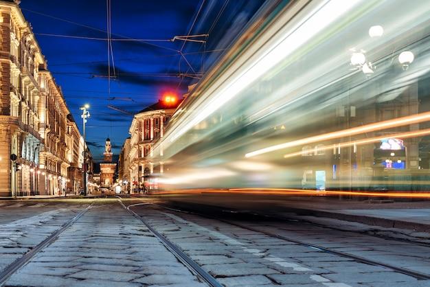 Трамвай в размытом изображении проезжает по торговой улице в центре милана в италии