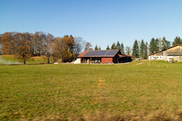 Спокойный осенний сельский пейзаж с сельскохозяйственными угодьями и полями, здания с солнечными батареями на крыше на фоне ясного голубого неба, австрия