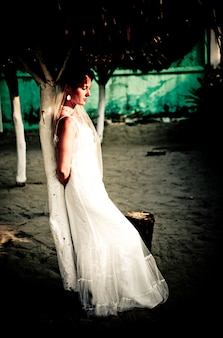 Tranquil bride in wedding dress leaning against post daydreaming
