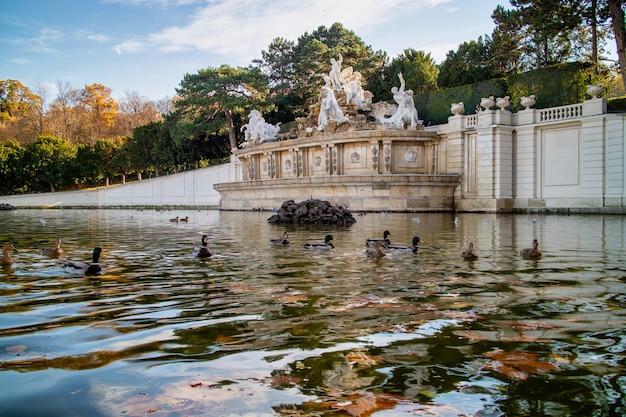 오스트리아 비엔나의 숀브룬 궁전 근처 공원에 있는 고대 동상과 연못에 떠 있는 오리가 있는 기념비의 고요한 가을 풍경