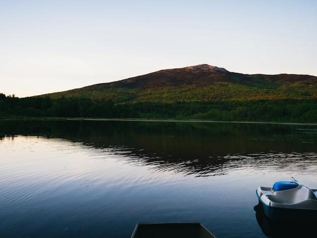 明るい空を背景に山のふもとにある静かな湖