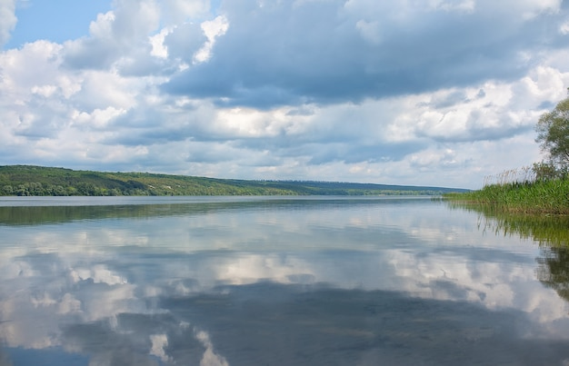 Спокойный пейзаж на озере, с ярким небом, белыми облаками и деревьями, симметрично отраженными в прозрачной голубой воде