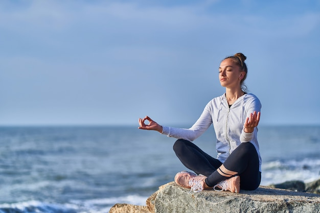 Tranquil one woman in lotus position meditates and relaxes on a cliff