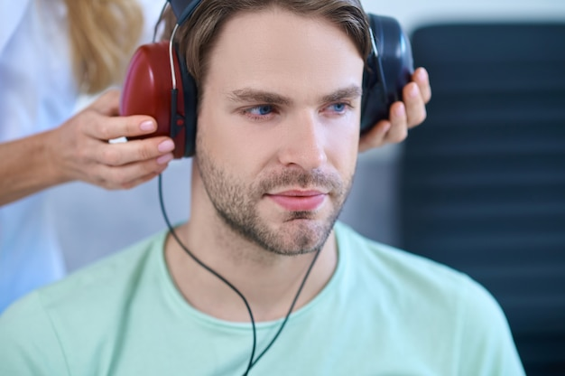 Tranquil patient wearing headsets during a hearing screening procedure
