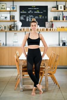 맨발로 테이블 근처에 서서 체육관에서 훈련하기 전에 휴식을 취하는 운동복을 입은 고요한 웃는 여성