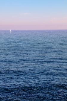 パステルピンクの空と穏やかな海、高角度の景色と静かな夕日の海景シーン