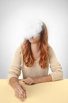 静かな女性が座って、テーブルで休んで喫煙。
