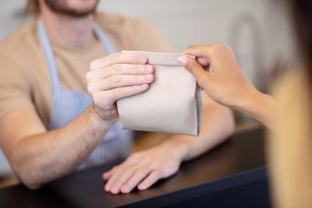 転送モーメント。転送時にカウンターの上に小さな紙袋を持っている男性と女性の手、顔なし