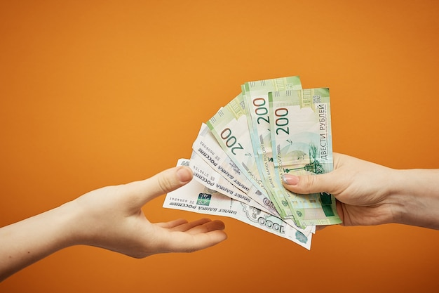 Transfer money to each other, two hands and cash on orange.
