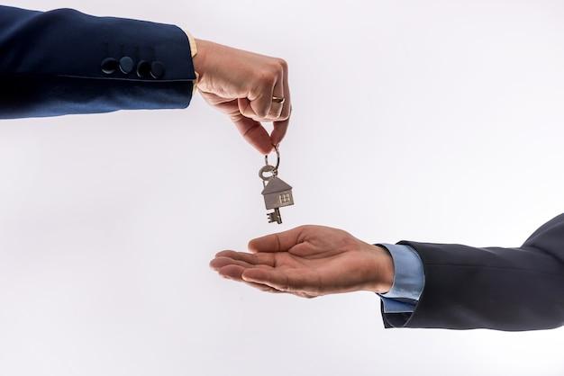 白い背景で隔離のアパートを借りたり売ったりする2人のビジネスマンの間の家の譲渡。販売コンセプト