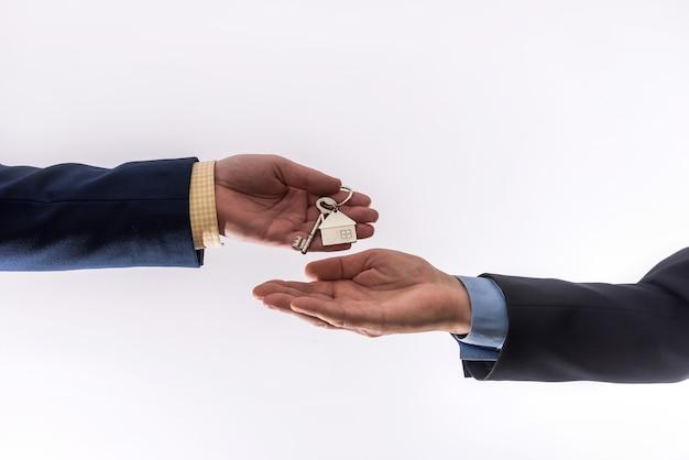 흰 벽에 고립 된 아파트를 임대하거나 판매하는 두 비즈니스 사람 사이의 집 양도. 판매 개념