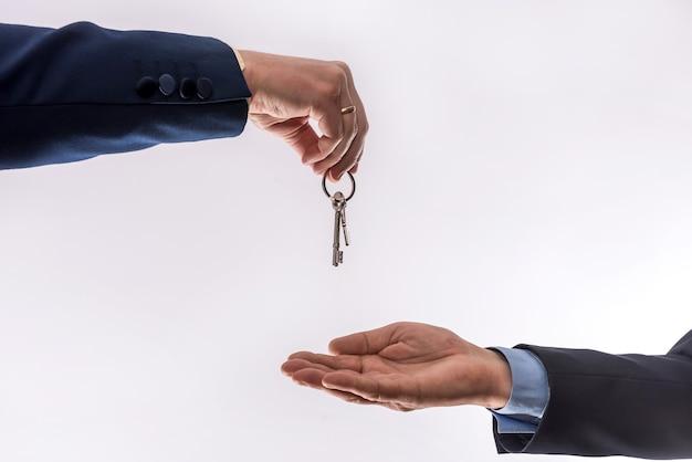 白い壁に隔離されたアパートを借りたり売ったりする2人のビジネスマンの間の家の譲渡。販売コンセプト
