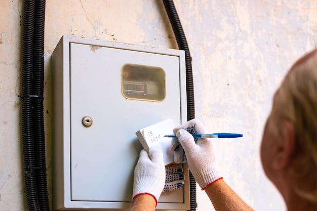 Передача показаний электросчетчика. мужчина записывает цифры в киловаттах.