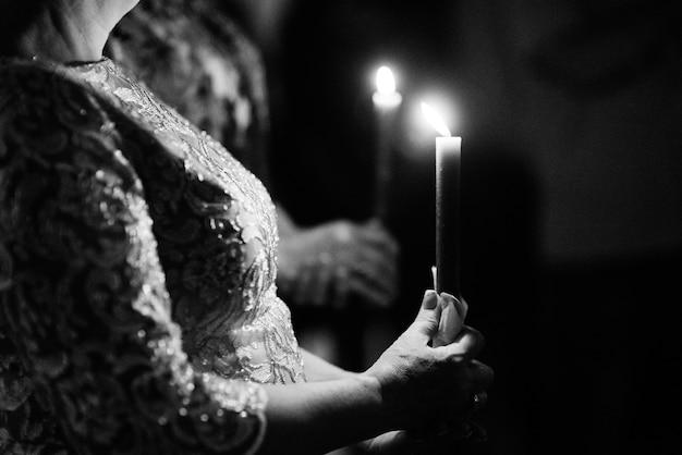 キャンドルの助けを借りて母親から新婚夫婦に結婚式の火を移す