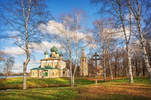가을 태양 광선에 우글 리치 크렘린에있는 공원의 나무들 사이 종탑이있는 변형 성당