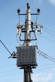 Трансформатор установлен на шесте на голубом небе