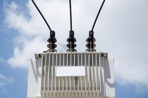 Трансформатор установлен на высоком фоне голубого неба.