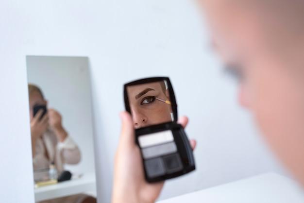 Трансгендер наносит макияж крупным планом