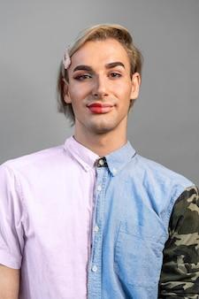 顔の半分に化粧をしているトランスジェンダーの男性