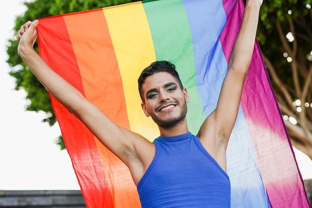 도시에서 lgbt 무지개 깃발을 들고 화장을 한 트랜스젠더 남자 - lgbtqia 개념
